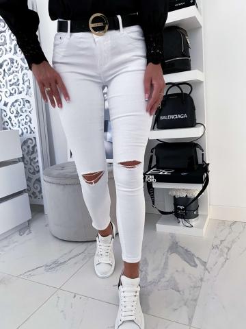 Białe spodnie z pęknięciem na kolanie